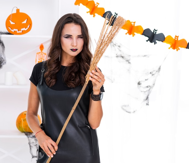 Mooie volwassen vrouw met halloween-bezem