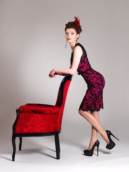 Mooie volwassen vrouw met mode kapsel en rode fauteuil vormt in de studio