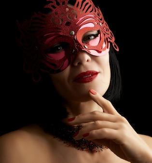 Mooie volwassen vrouw met zwart haar dat een rood glanzend carnaval-masker draagt