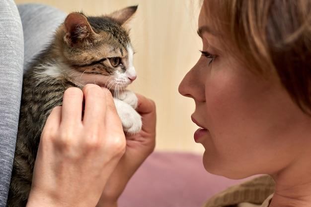 Mooie volwassen vrouw speelt met een kleine kat