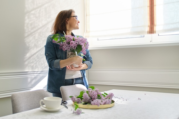 Mooie volwassen vrouw thuis met boeket van lila bloemen