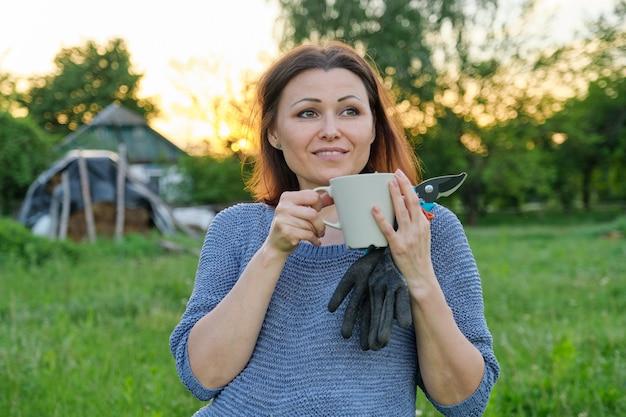 Mooie volwassen vrouw tuinman in handschoenen met snoeischaar met kopje kruidenthee rusten in de natuur, zonsondergang