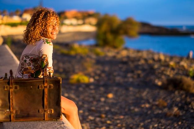 Mooie volwassen vrouw van middelbare leeftijd glimlacht en geniet van een vrijetijdsbesteding buitenshuis in de zomervakantie alleen op het strand - vrolijke dame gaat zitten in ontspannen tijd