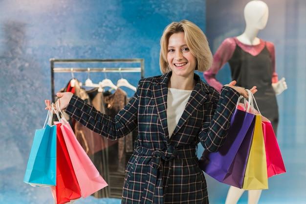 Mooie volwassen vrouwenholding het winkelen zakken