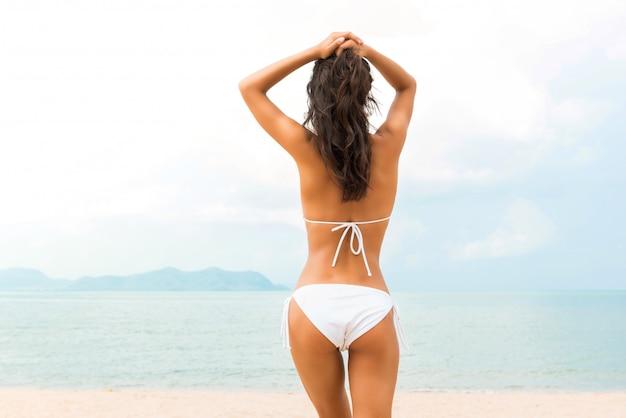 Mooie vormvrouw in het witte bikinizwempak stellen bij het strand