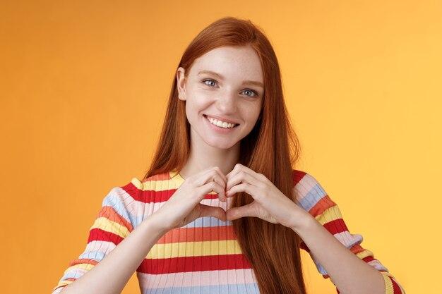 Mooie vriendelijk ogende charismatische glimlachende roodharige meid drukt genegenheid uit, liefde en vriendschap, grijnzend, toont hartteken op de borst met sympathie, belijdt romantische gevoelens, staande oranje achtergrond.