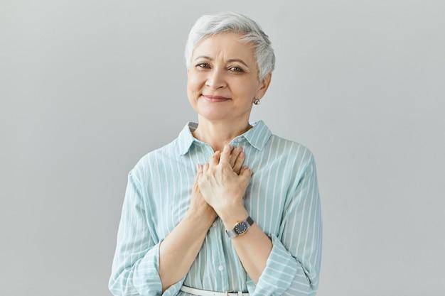 Mooie vriendelijk ogende vrouw van middelbare leeftijd met een oprechte glimlach, dankbaarheid uitend, dankbaar gevoel, haar hart gevuld met liefde tonen, handen op haar borst houdend. positieve echte menselijke gevoelens
