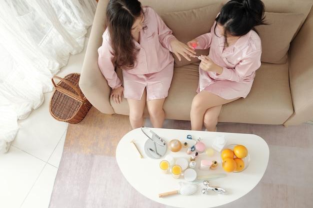 Mooie vrienden in zijden pyjama's die thuis op de bank zitten, elkaar manicuren en roddelen, van bovenaf bekijken