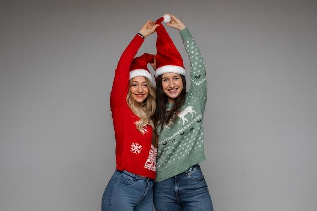 Mooie vriendinnen die de hoed van de kerstman omhoog trekken.