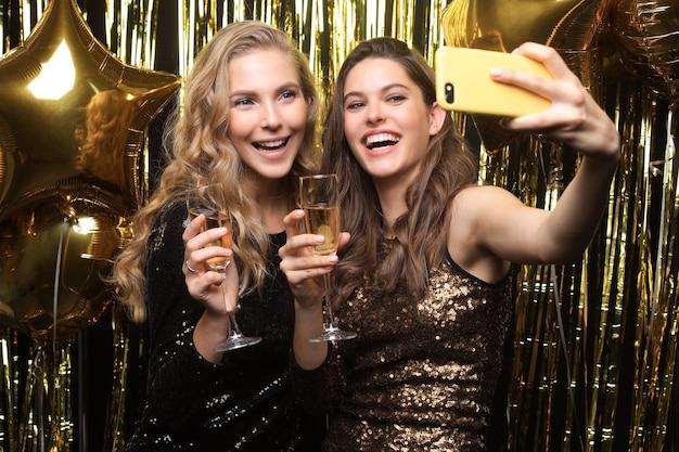 Mooie vriendinnen in een goed humeur nemen selfie op feestje op gouden achtergrond.
