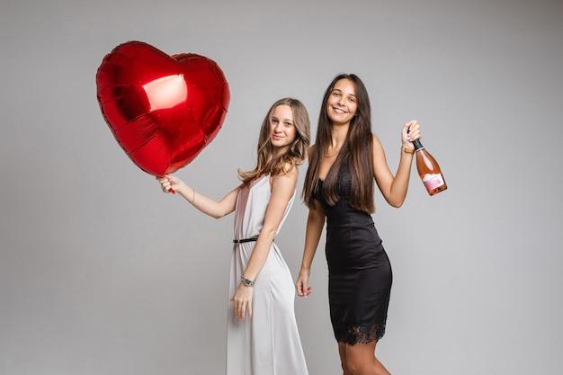 Mooie vriendinnen in jurken met champagne en een grote rode ballon, geïsoleerd op een witte muur