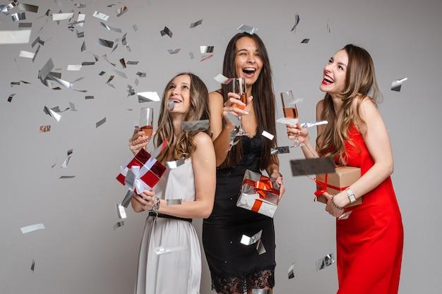 Mooie vriendinnen in jurken met champagne en veel confetti om hen heen, op wit
