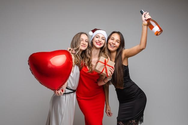 Mooie vriendinnen in jurken met een cadeautje, geïsoleerd op een witte muur