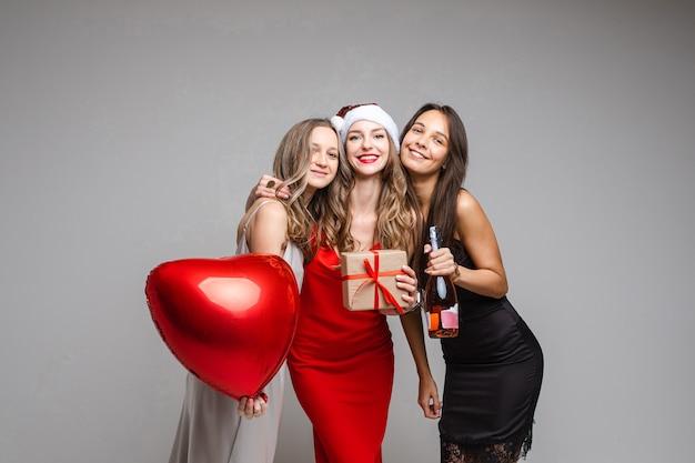 Mooie vriendinnen in jurken met een cadeautje, op wit