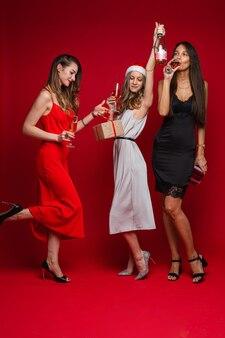 Mooie vriendinnen in jurken met een cadeautje verheugt zich samen, geïsoleerd op een witte muur