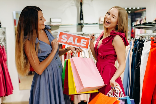 Mooie vriendinnen in winkels kochten kleding tegen gereduceerde prijzen