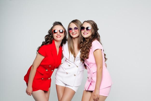 Mooie vriendinnen in zonnebril en modieuze pakken over whit