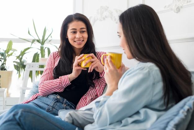 Mooie vriendinnen praten en hebben warme dranken