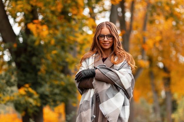 Mooie vrij gelukkige vrouw model met bril in een jas in een gebreide sjaal geniet van ontspannen in het herfst park tussen een boom met oranje gebladerte. vrolijk meisje staat in het park en lacht schattig.