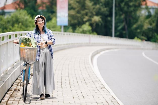 Mooie vrij jonge aziatische vrouw die in hoed langs weg met fiets loopt