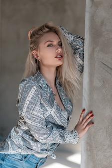Mooie vrij sexy jonge vrouw blonde in een elegante zomer shirt met een patroon in stijlvolle spijkerbroek staat in de buurt van de grijze betonnen muur binnenshuis op een zonnige dag