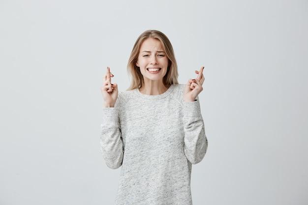 Mooie, vrijgevochten jonge vrouw met geverfd haar in losse trui kruist vingers, bidt voor belangrijke gebeurtenis, wenst geluk, hoopt op overwinning en succes. vrouw die hoopvol voelt, wachtend op wonder