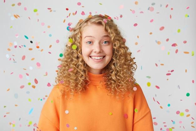 Mooie vrolijke, aardige blondine met blauwe ogen staat onder vallende confetti, glimlachend en toont gezonde tanden