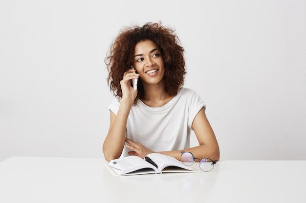Mooie vrolijke afrikaanse onderneemster die op telefoon over witte muur spreekt.