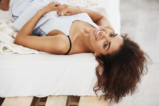 Mooie vrolijke afrikaanse vrouw in nachtkleding glimlachen liggend op bed thuis.
