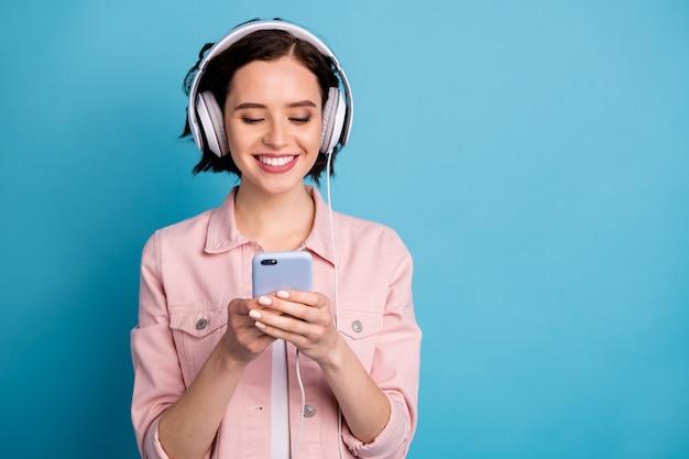 Mooie vrolijke dame houd telefoon luister koptelefoon muziek