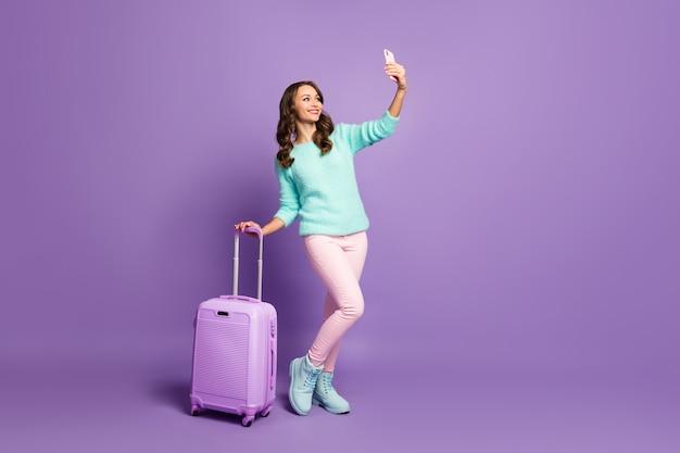 Mooie vrolijke dame lopen luchthavenregistratie rollende koffer blog maken selfies dragen fuzzy pasteltrui roze broek laarzen.