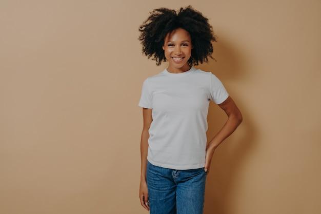 Mooie vrolijke donkere gevilde vrouw in casual outfit glimlachend in de camera, vrolijke afrikaanse vrouw in witte t-shirt en spijkerbroek die positieve emoties uitdrukt, poseren tegen beige achtergrond in studio