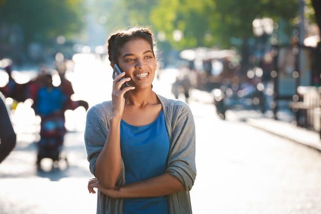 Mooie vrolijke donkere huid meisje sprak over de telefoon