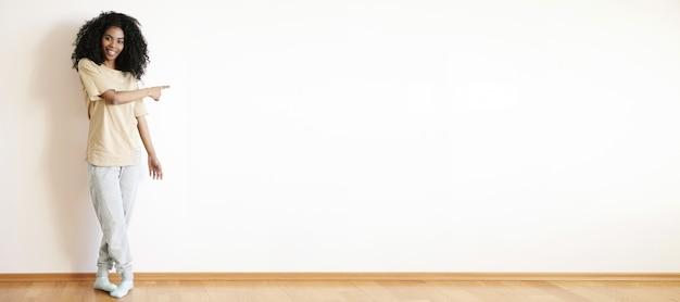 Mooie vrolijke jonge afrikaanse vrouw met krullend haar gekleed terloops glimlachend gelukkig staande op witte lege muur en iets erop wijzend met haar wijsvinger