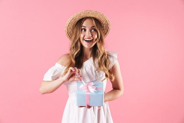 Mooie vrolijke jonge blonde meid die een zomerjurk draagt, geïsoleerd over een roze muur, met de huidige doos