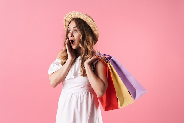 Mooie vrolijke jonge blonde meid met een zomerjurk die geïsoleerd over een roze muur staat en boodschappentassen draagt