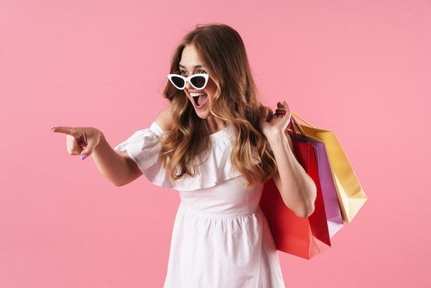 Mooie vrolijke jonge blonde meid met een zomerjurk die geïsoleerd staat over een roze muur, boodschappentassen draagt, wegwijst