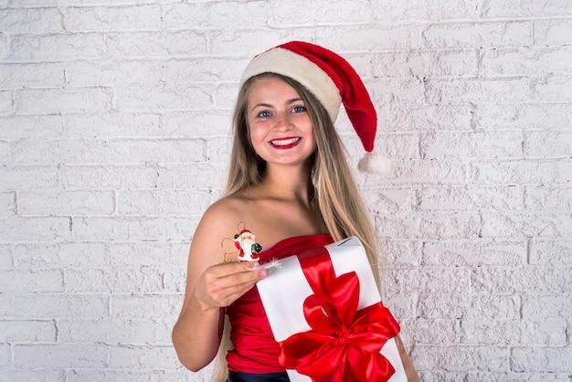 Mooie vrolijke jonge vrouw die in rode kleding grote rode gift of heden houdt