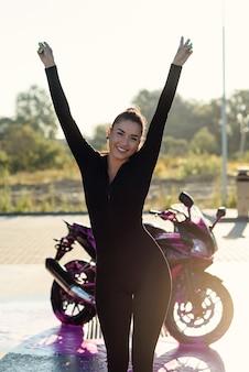 Mooie vrolijke jonge vrouw in strak zwart pak hief handen omhoog in de buurt van sport motorfiets bij self service car wash