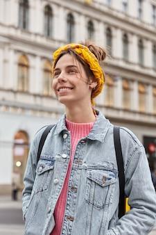 Mooie vrolijke jonge vrouw loopt langs straat, draagt gele hoofdband, spijkerjasje