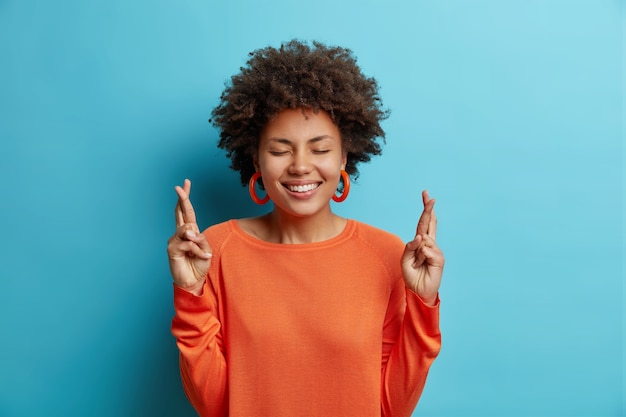 Mooie vrolijke jonge vrouw met brede perfecte glimlach houdt vingers gekruist gelooft in geluk draagt oranje trui geïsoleerd over blauwe muur