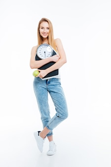 Mooie vrolijke jonge vrouw poseren met schalen en groene appel op witte achtergrond