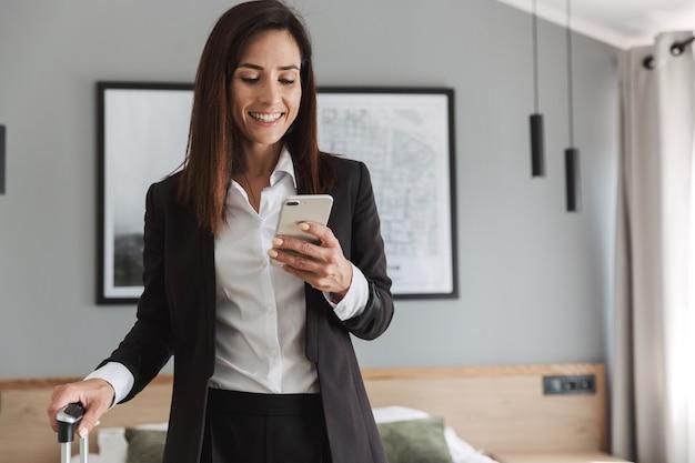 Mooie vrolijke jonge zakenvrouw in formele kleding binnenshuis thuis met koffer met behulp van mobiele telefoon.