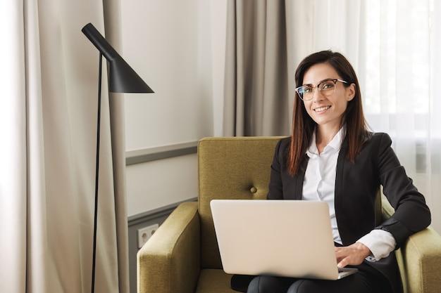 Mooie vrolijke jonge zakenvrouw in formele kleding binnenshuis thuis werken met laptopcomputer.
