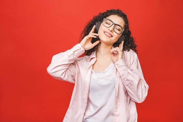 Mooie vrolijke krullende brunette student meisje, luisteren naar muziek, dansen