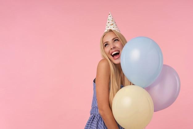 Mooie vrolijke langharige jongedame in blauwe zomerjurk en kegel hoed tonen gelukkige reactie op het krijgen van geweldig cadeau, poseren op roze achtergrond met veelkleurige helium ballonnen