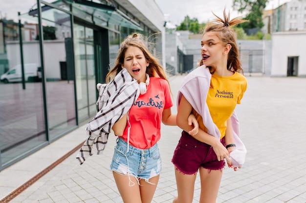 Mooie vrolijke meisjes in trendy zomerkleding lopen langs de winkel en praten over iets interessants