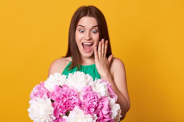 Mooie vrolijke meisjestribunes die over gele studio worden geïsoleerd, stelt glimlachend en houdend boeket van pioenbloemen