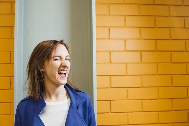 Mooie vrolijke moderne gekke vrouw op gele bakstenen muur