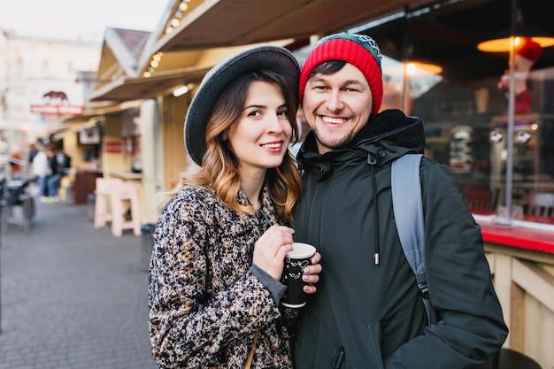 Mooie vrolijke paar chillen, knuffelen op straat in de kersttijd. ware liefdesemoties, plezier hebben, genieten van samenzijn, daten, romantische relaties, samen gelukkig zijn.